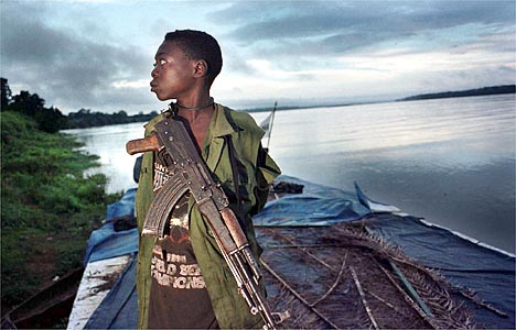DONGO, CONGO.  SEPTEMBER 15, 2000: A young soldier with the MLC  (Movement for the Liberation of Congo), a rebel army, rides atop a boat on the Ubangi River approaching the remote village of Dongo in northwestern Congo, where they recently made a significant advance against President Laurent Kabila's army.   (Photo: Tyler Hicks/Liaison).