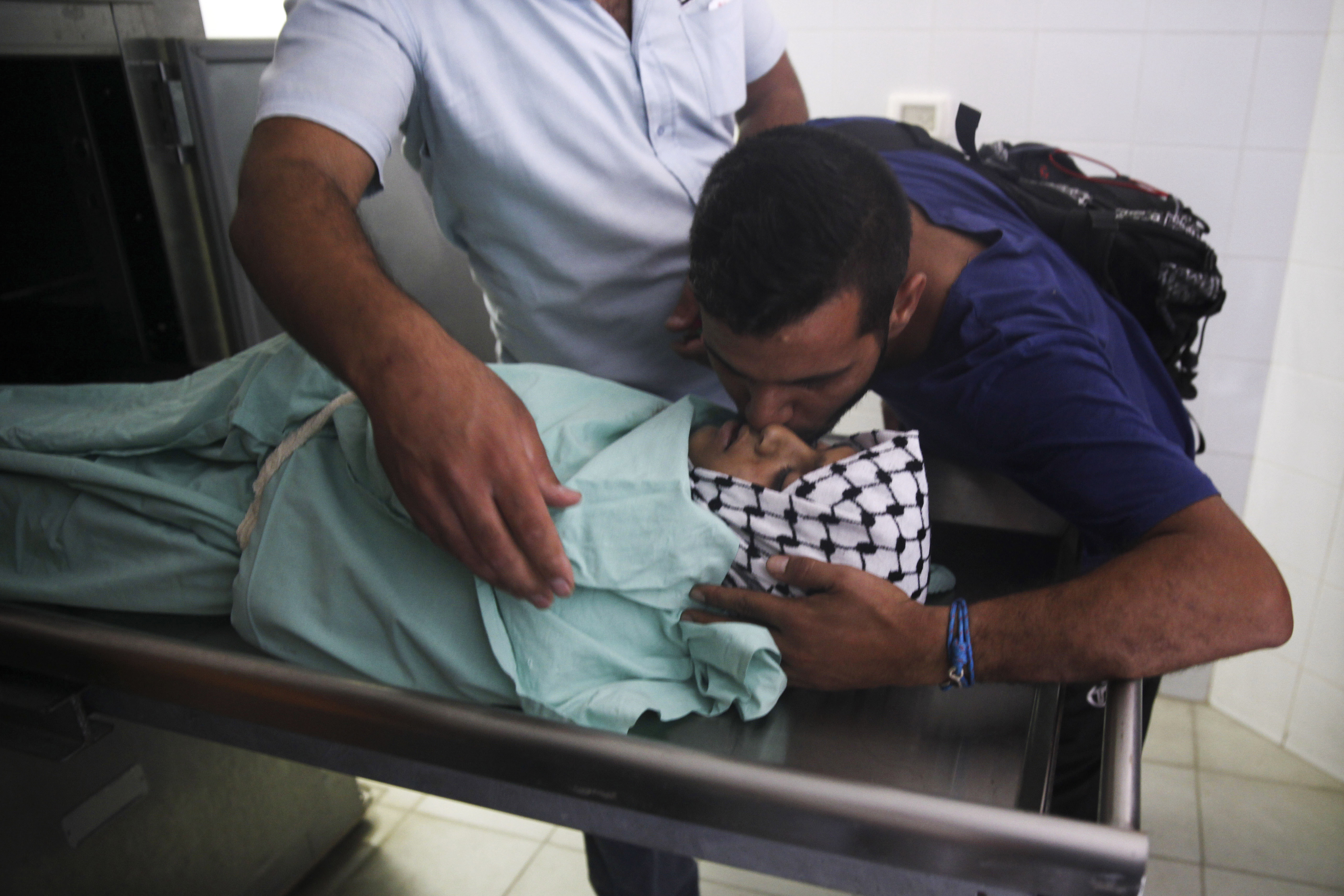 A man kisses 13-year-old Palestinian Abdel Rahman Shadi in a morgue in the town of Bethlehem, West Bank, Monday, Oct. 5, 2015. Shadi died after being hit by a live bullet to the chest during clashes between Palestinians and Israeli security forces, a doctor at a hospital near the clashes said. (AP Photo/Mahmoud Illean)
