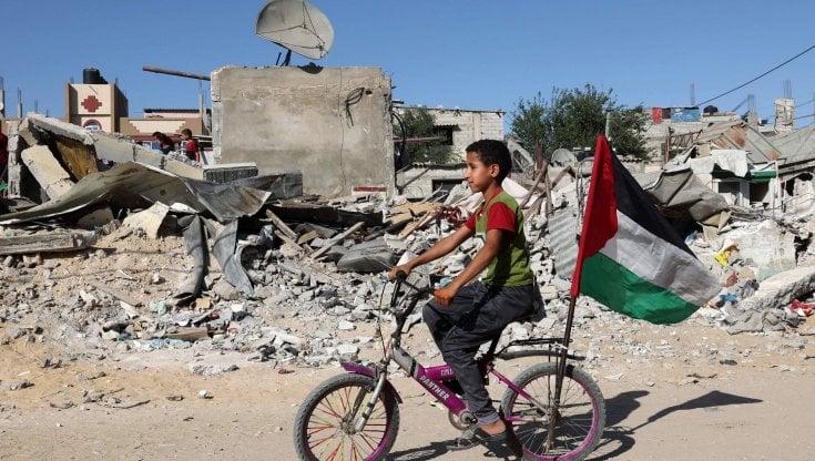 Un bambino in bicicletta di fronte alle macerie di un edificio distrutto a Gaza (afp)
